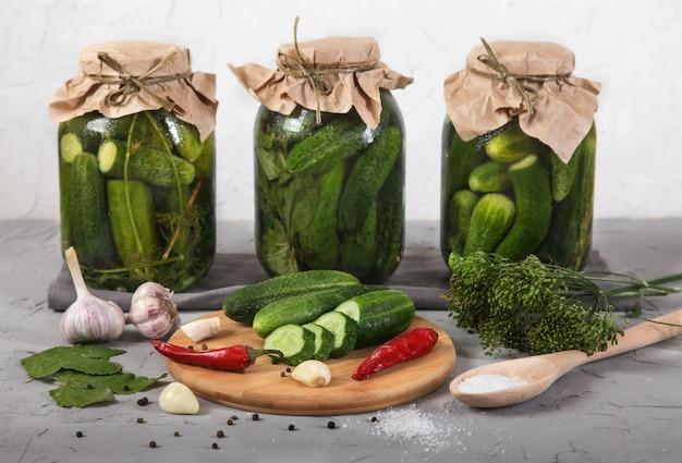 Drie grote glazen potten met gefermenteerde komkommers, gesneden komkommers op een houten plank staan op een betongrijs.