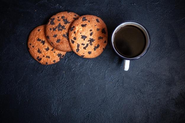 Drie grote koekjes en een kopje koffie op een zwarte betonnen achtergrond. koekjes met chocolade. afbeelding voor inscriptie