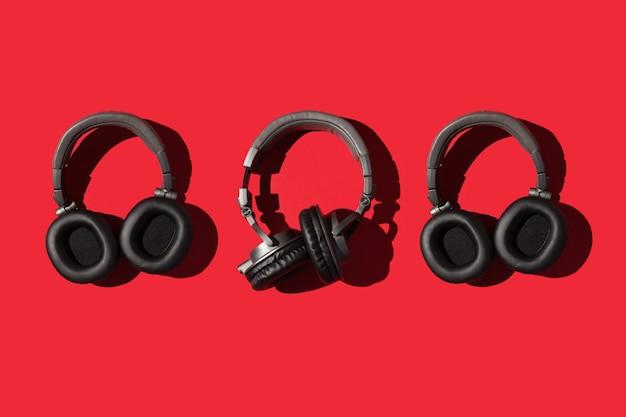 Drie grote koptelefoons op een rode achtergrond muziek concept