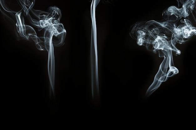 Drie grote silhouetten van rook op zwarte achtergrond
