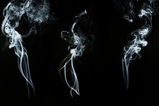 Drie grote silhouetten van witte rook
