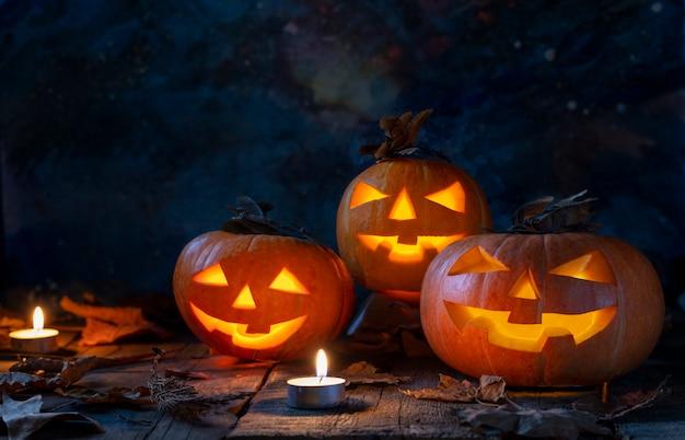 Drie halloween-pompoenen hoofdhefboom o lantaarn op houten lijst in een mysticusbos bij nacht.