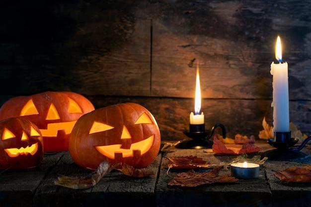 Drie halloween-pompoenen hoofdhefboom o lantaarn op houten lijst.