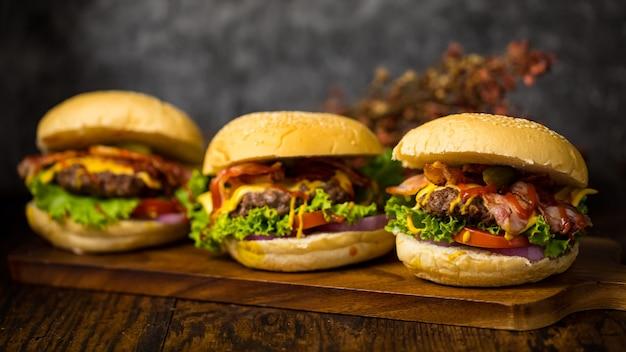 Drie hamburgers met runderhamburger kotelet, gebakken ui, spinazie, ketchupsaus en kaas, geserveerd op houten snijplank over donkere houten achtergrond.