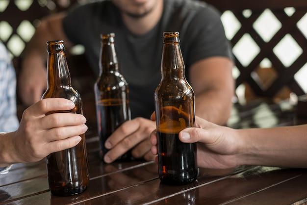 Drie handen met bierflessen op tafel