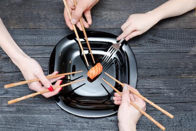Drie handen met stokjes, één met vork en sushi.