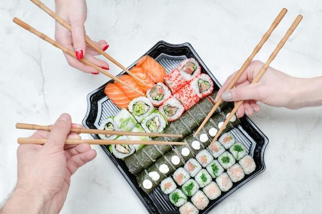 Drie handen met stokjes en sushi set. bovenaanzicht