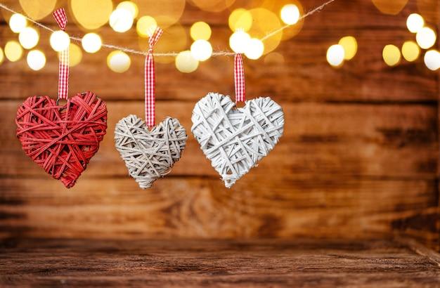 Drie handige bewerkte harten die op houten met bokeh hangen.