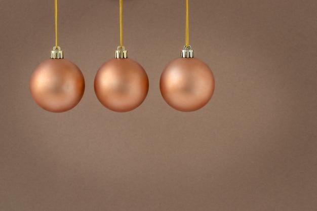 Drie hangende kerstversieringen op een bruine achtergrond