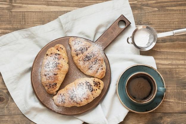 Drie heerlijke vers gebakken chocolade croissants en kopje koffie op snijplank. bovenaanzicht ontbijt concept.