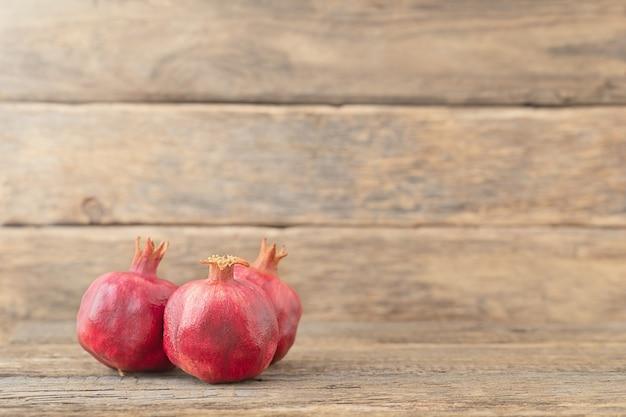 Drie hele rijpe granaatappels die op houten achtergrond liggen
