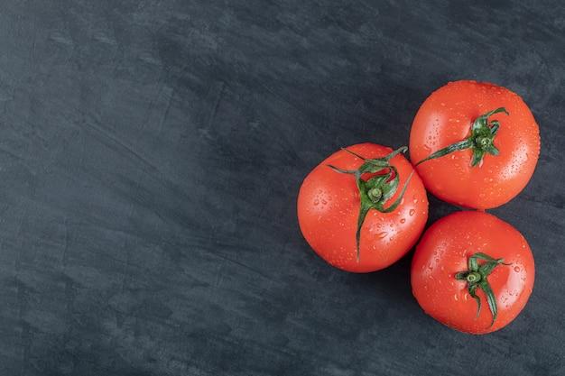Drie hele verse tomaten op een donkere achtergrond.