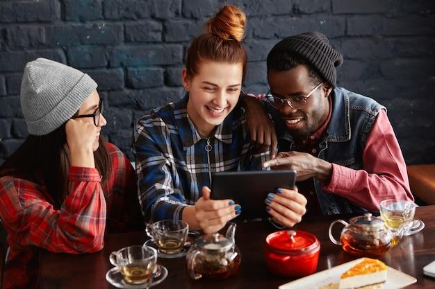 Drie hipsters die lol hebben in de koffieshop