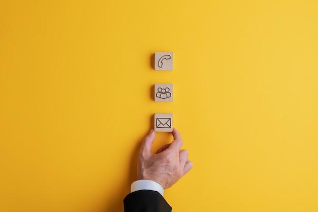 Drie houten blokken met contact- en communicatiepictogrammen erop plaatsen op een felgele achtergrond