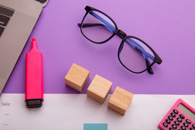 Drie houten blokken op een roze tafel. creatieve werkplek