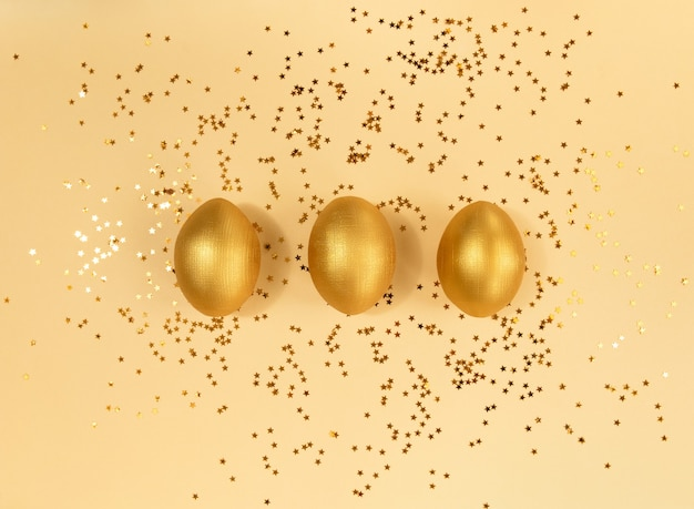 Drie houten gouden paaseieren en confetti op een beige achtergrond.
