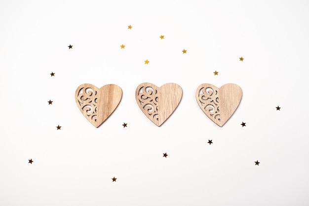 Drie houten harten en kleine gouden sterren op wit. valentijnsdag concept.