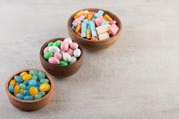 Drie houten kommen met kauwgom en snoepjes stenen tafel.