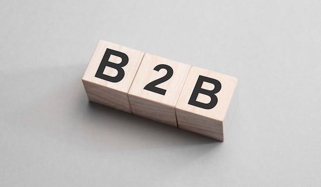 Drie houten kubussen met letters b2b op grijze achtergrond