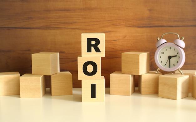 Drie houten kubussen verticaal gestapeld op een bruine achtergrond vormen het woord roi.