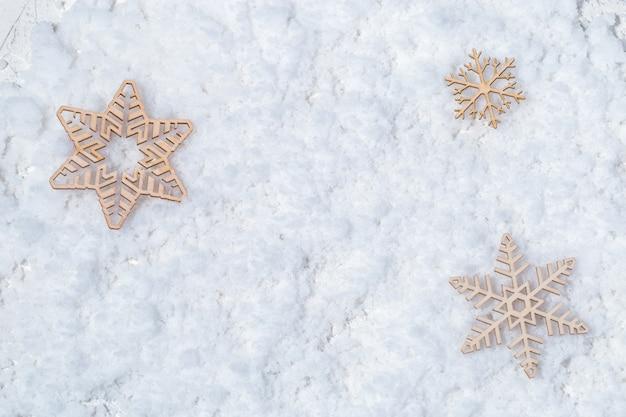 Drie houten sneeuwvlokken op sneeuw