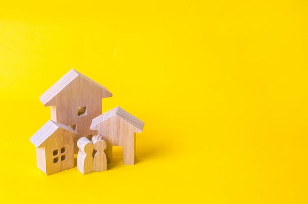 Drie huizen op een gele achtergrond. kopen en verkopen van onroerend goed, bouw.