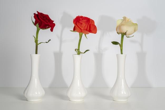 Drie identieke witte vazen met rode, oranje en witte rozen. hard licht