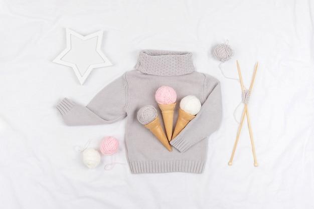 Drie ijs van garen en wafel kegels op een grijze gebreide trui, houten breinaalden en ster op witte achtergrond. breien, hobby en handgemaakt concept. bovenaanzicht plat lag.