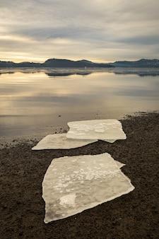 Drie ijsschotsen op donker zand op noors strand. kalme zee, mist en mist. hamresanden, kristiansand, noorwegen