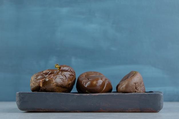 Drie ingelegde aubergines op het bord
