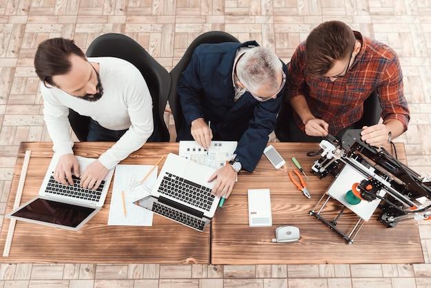 Drie ingenieurs zitten aan de tafel met een laptop