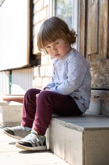 Drie jaar oude jongen zittend op trappen.