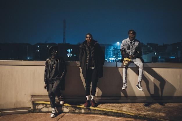 Drie jonge afrikaanse mannen die samen poseren in een parkeergarage