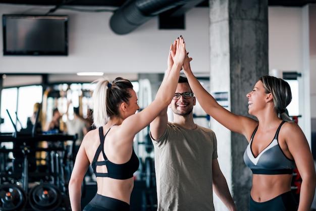 Drie jonge atletische mensen in sportkleding geven hoge vijf in de sportschool.