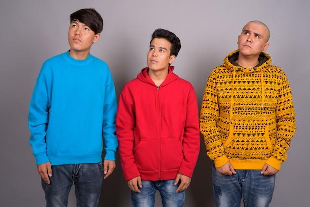 Drie jonge aziatische mannen dragen warme kleding tegen de grijze muur