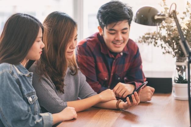 Drie jonge aziatische mensen die samen dezelfde mobiele telefoon gebruiken en bekijken
