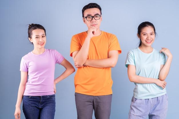 Drie jonge aziatische mensen die zich voordeed op blauwe achtergrond
