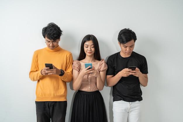 Drie jonge aziatische mensen gebruiken hun smartphones terwijl ze staan
