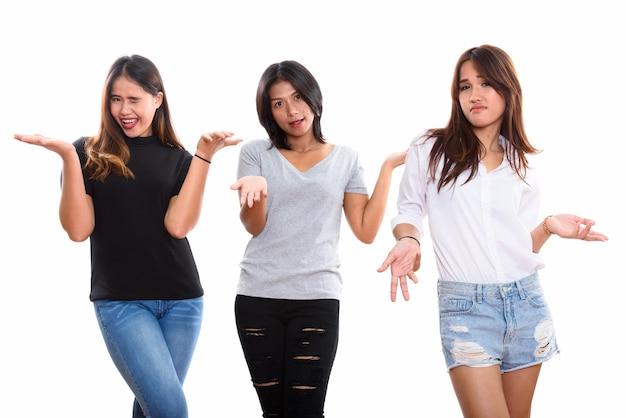 Drie jonge aziatische vrouw vrienden op zoek verward geïsoleerd