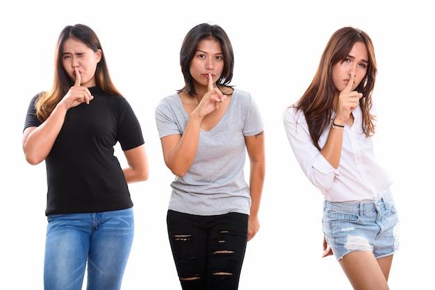 Drie jonge aziatische vrouwenvrienden met vinger op lippen