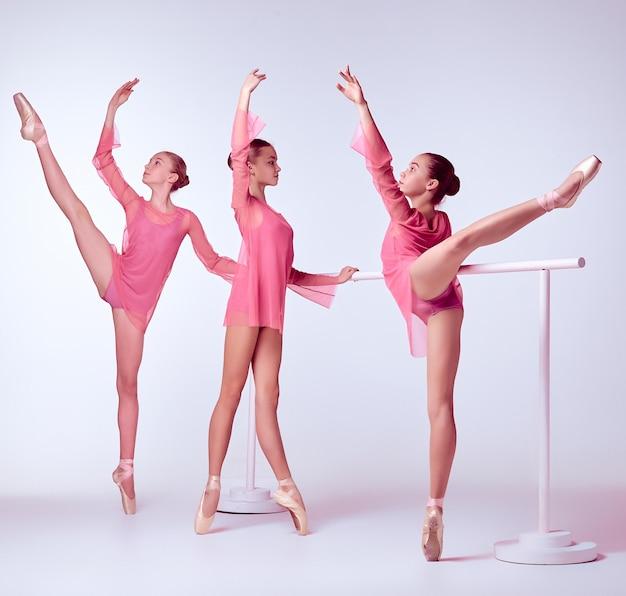Drie jonge ballerina's die zich uitstrekken op de bar op beige achtergrond