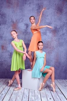 Drie jonge ballerina's in kleurrijke jurken poseren op lila houten vloer achtergrond