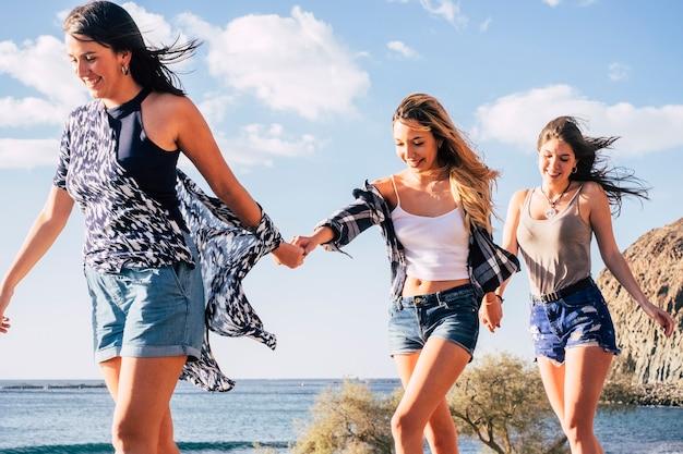 Drie jonge blanke mooie meisjes lopen samen en nemen elkaar de hand glimlachend en lachend. vrolijk concept van gelukkige vrouwen in vrijetijdsbesteding in de buitenlucht in de buurt van de oceaan en de bergen