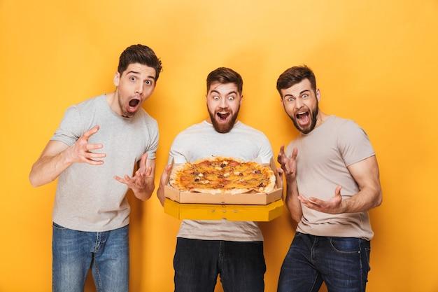 Drie jonge blije mannen die een grote pizza houden