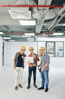 Drie jonge civiel ingenieurs bespreken regeling van servicelijnen op laptop scherm tijdens het werken in het gebouw in aanbouw