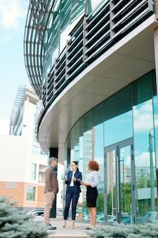 Drie jonge elegante zakenpartners staan bij een hoog modern kantoorgebouw terwijl ze de werkmomenten bespreken