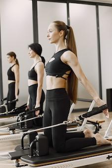 Drie jonge fit vrouwen trainen in de sportschool. vrouwen die zwarte sportkleding dragen. kaukasische meisjes oefenen met apparatuur.