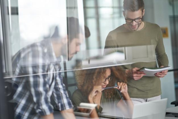 Drie jonge gefocuste collega's of collega's die naar een laptop kijken en een nieuw project bespreken terwijl