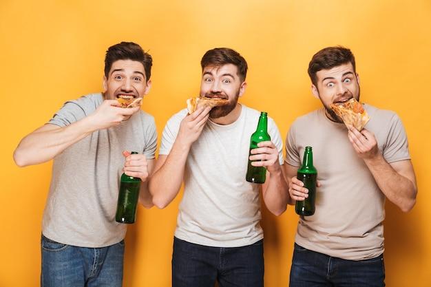 Drie jonge gelukkige mannen die pizza eten en bier drinken