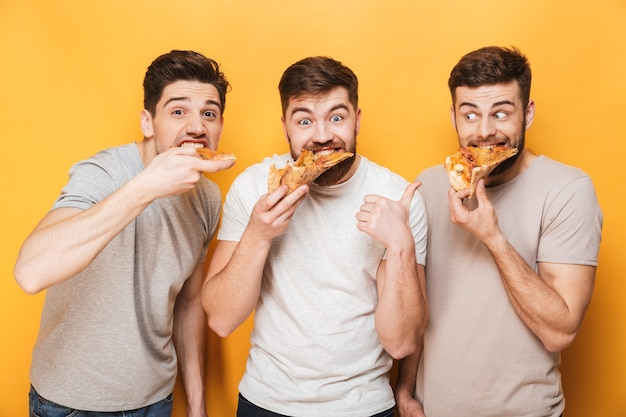 Drie jonge gelukkige mannen die pizza eten